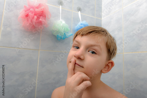Fotografía The child in the shower room thinks what kind of washcloth he should choose and what he will do now