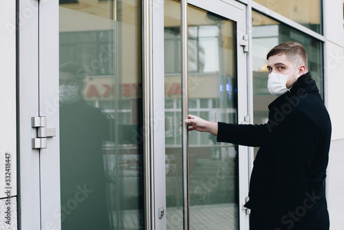 Fotomural Young man opening door to his office wearing surgical face mask to protect from