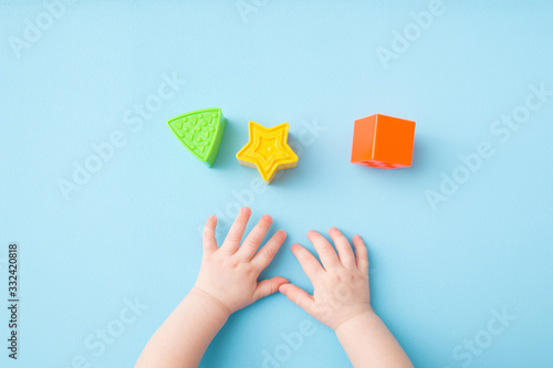 Fotografia, Obraz Baby hands playing with green triangle, yellow star and orange square shapes on light blue table background