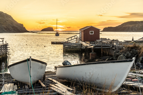 Small fishing boats beached on a wooden ramp and a small boathouse and a doc in Canvas Print