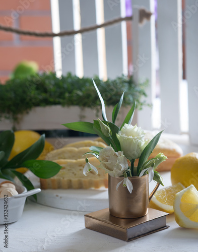 Photo Lemon airy biscuit on a white tray. Table with flowers