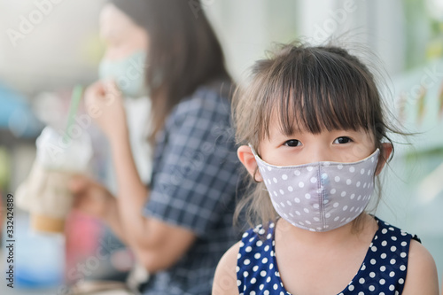 Fototapeta Little girl has fabric mask protect herself from Coronavirus,New Normal child leave the house with a mask on her nose for safety outdoor activity after COVID-19 outbreak,illness or Air pollution obraz
