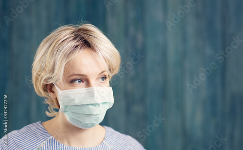 young woman in medical face protection mask indoors on blue background Fototapete