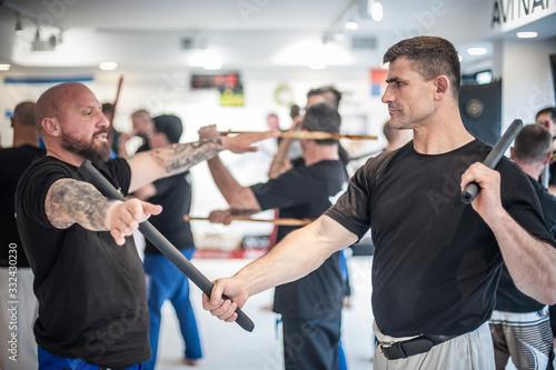 Obraz Large group of students practice filipino eskrima stick fight techniques - fototapety do salonu