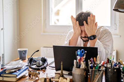 Obraz Tired frustrated businessman working from home online sitting at home office with laptop during quarantine and self isolation period at pandemic. Crisis management. Despair of market falling down. - fototapety do salonu