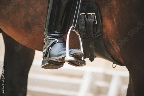 The black booted rider's foot bases on a metal stirrup, which is worn as a sporting gear on a Bay horse Canvas Print