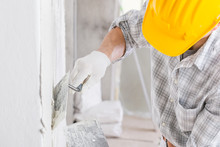 Builder Using A Trowel To Add Plaster To A Wall