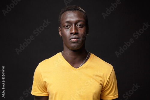 Obraz Handsome young african american man guy in yellow t-shirt posing isolated on black wall background studio portrait. People sincere emotions, lifestyle concept. Mock up copy space. Looking camera. - fototapety do salonu