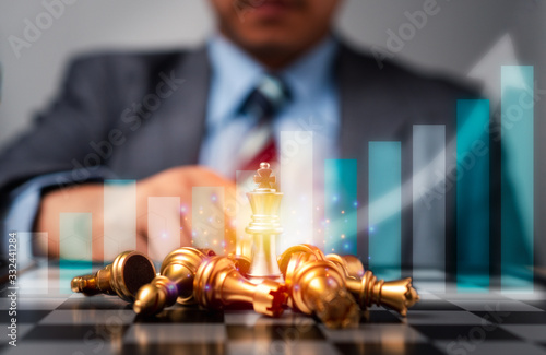 Obraz Selective focus of golden chess and success business graph in front of professional business analysis man. Concept of leadership must-have solution for the financial crisis, Investment planning - fototapety do salonu