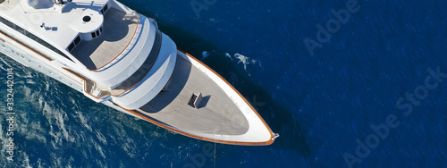 Aerial drone ultra wide photo of luxury mega yacht with wooden deck anchored in deep blue sea of Mykonos island, Cyclades, Greece