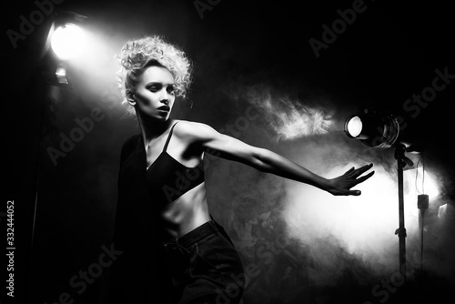 Fotografie, Tablou A beautiful blonde girl with an elegant hairstyle and large breasts, wearing a bra, trousers and a blazer, artistically poses in the rays of spotlights in the smoke