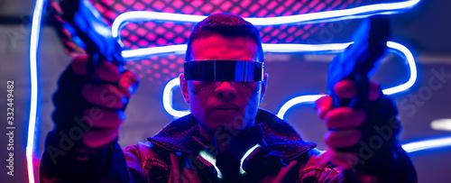 Obraz panoramic shot of mixed race cyberpunk player in futuristic glasses holding guns near neon lighting - fototapety do salonu
