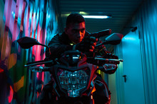 Bi-racial Cyberpunk Player On Motorcycle Aiming Gun On Street With Graffiti