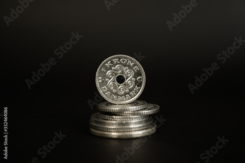 Fotografie, Obraz One Danish krone coin standing on stack of coins against black background