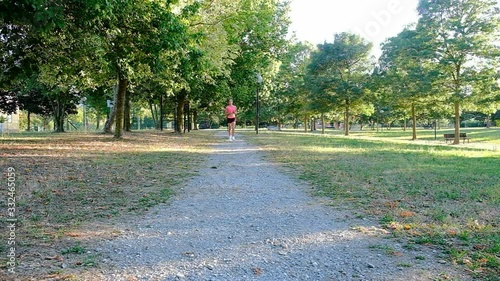 Young woman runner training in summer park. Close up fitness woman jogging outdoor. Tired girl jogger breathing after run marathon in park. Morning running concept