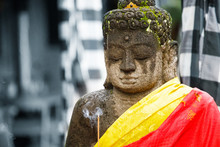 Portrait Of Stone Buddha Statue In Yellow And Red Shawl