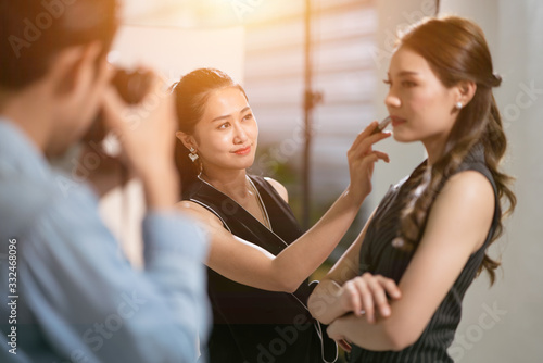 Selective focus of happy Asian makeup artist putting on more lipstick to the actress or model behind the scene, concept of pride of profession, professional occupation, skilled professional career Canvas Print