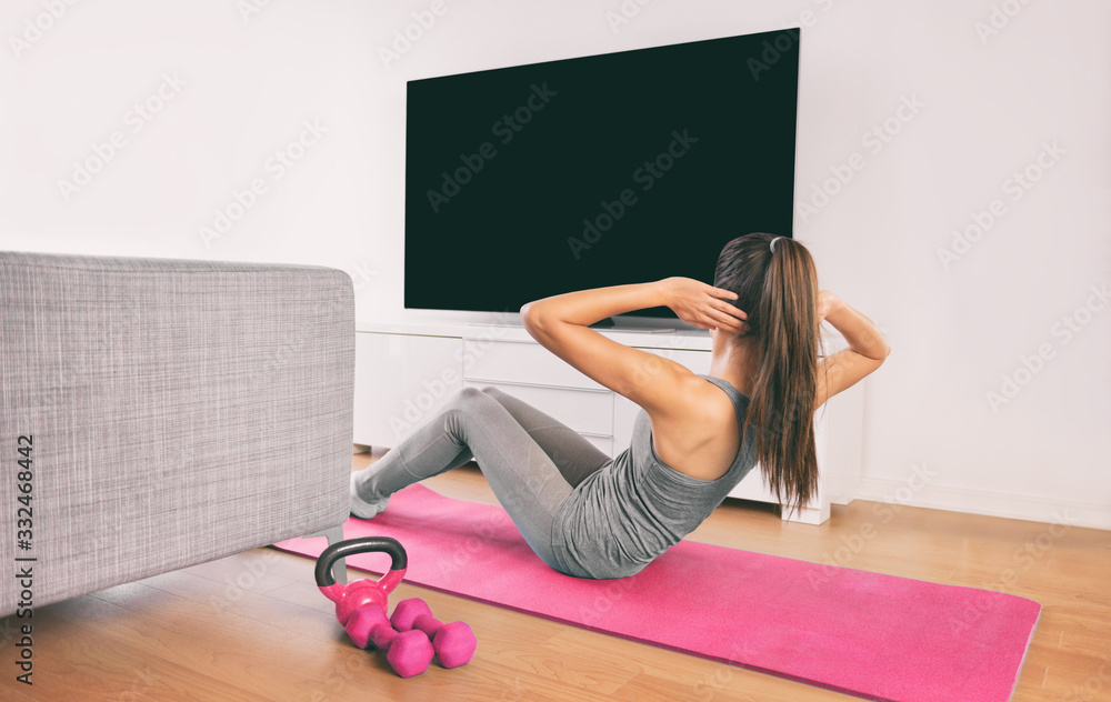 Fototapeta Home fitness woman doing strength training abs situps bodyweight floor exercises watching online livestream workout web videos casted on smart tv in living room of house or apartment.