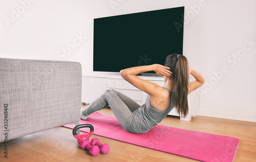 Fototapeta Home fitness woman doing strength training abs situps bodyweight floor exercises watching online livestream workout web videos casted on smart tv in living room of house or apartment. obraz