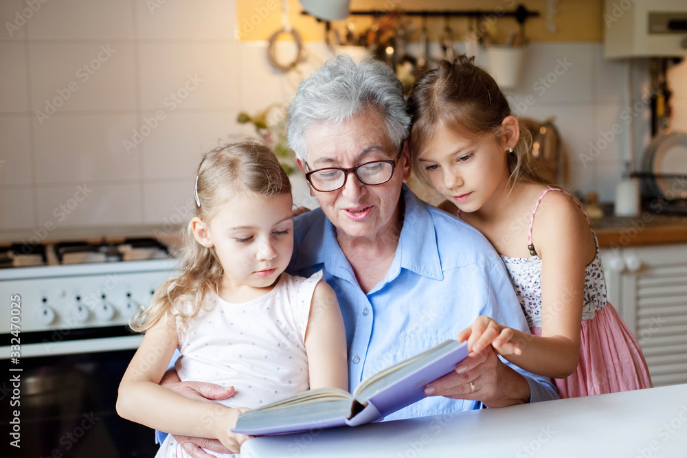 Fototapeta Reading book at home. Grandmother reads fairy tale. Kids listen to granny story in cozy kitchen. Happy family leisure. Children and senior woman togetherness. Lifestyle authentic moment.