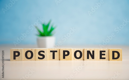 Photo Postponed - words from wooden blocks with letters, postponed concept, top view b
