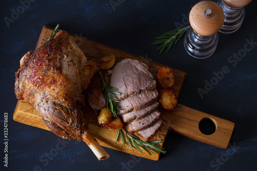 Roast leg of lamb with potatoes and rosemary on dark background Canvas Print