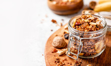 Homemade Toasted Granola With Honey, Walnuts, Flax And Sesame Seeds In A Glass Jar Closeup, Selective Focus, Free Space For Text. Healthy Vegetarian Breakfast, Copy Space.