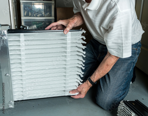 Fotografía Senior caucasian man checking a clean folded air filter in the HVAC furnace syst
