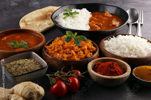 Obraz Chicken tikka masala spicy curry meat food in pot with rice and naan bread. indian food on table - fototapety do salonu