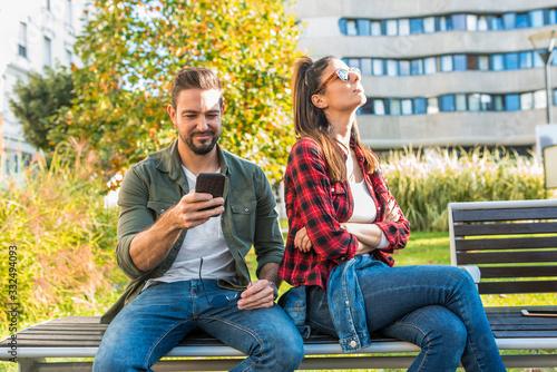 Photo A girlfriend being annoyed by her boyfriends smartphone usage.