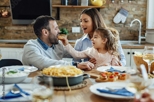Fotomural Young parents and their daughter enjoying in family lunch at home