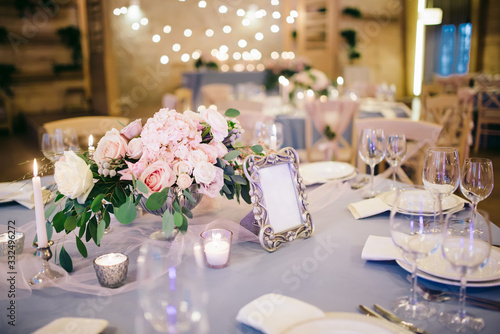 Fototapeta flower arrangement stands on the table in wedding banquet area on a blue tablecloth, the table is decorated with candles, there are plates, glasses, cutlery obraz