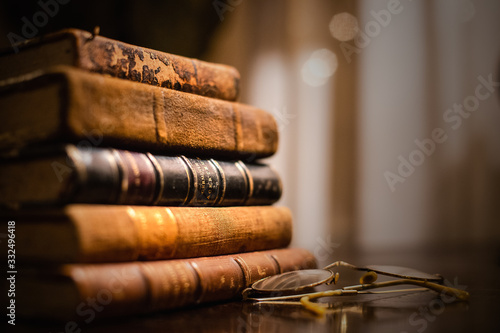 Obraz A vintage pile of five old brown leather books with eye glasses on a wood table. - fototapety do salonu