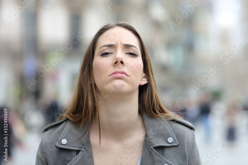 Disappointed woman looking at camera on street Fototapet