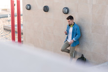 Smart Stylish Man In Bright Headphones Surfing Mobile Phone While Leaning On Marble Wall In Sunny Day