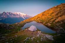 From Above Small Tent And Clear Lake Reflecting Sky High In Mountains In Sunny Day In Chamonix, Mont-Blanc