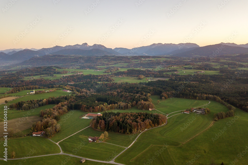 Aerial view of small scattered farm houses with red tiled roofs among green farming fields and distant mountain forest in summer.