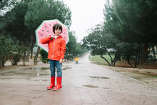 Active Kid With Watermelon Styles Open Umbrella In Red Raincoat And Rubber Boots Looking At Camera In Park Alley In Gray Day