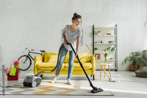 Fotografiet happy girl cleaning carpet with vacuum cleaner