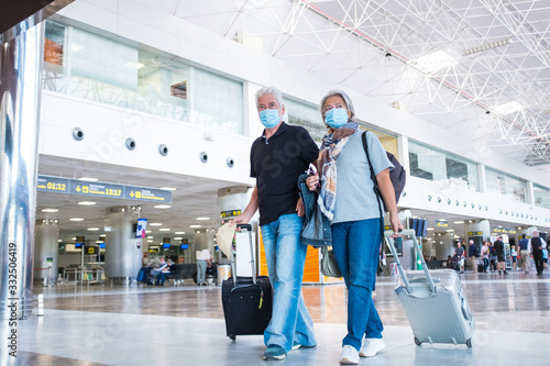 Obraz couple of two seniors or mature people walking in the airport going to their gate and take their flight wearing medical mask to prevent virus like coronavirus or covid-19 - carrying luggage or trolley - fototapety do salonu
