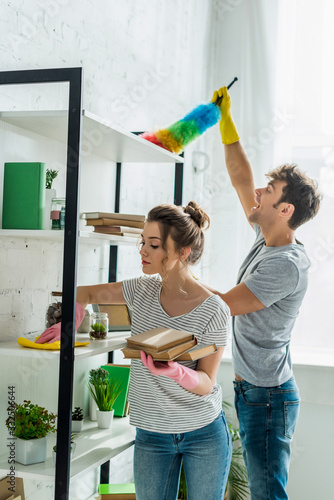 attractive girl in rubber gloves holding books while cleaning shelve with rag near man - 332506644