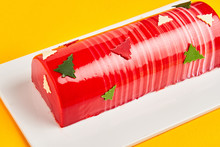 From Above Delicious Cake With Red Icing And Christmas Trees Placed On Board On Yellow Background