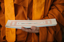 Crop Tibetan Buddhist Monk In Orange Clothes Holding Paper With Holy Ritual Text