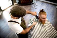 From Above Modern Hairdresser Barber Cutting A Adult Man Redhead's Hair In Barber Chair