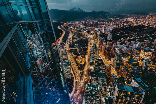 From above magnificent view night city from viewpoint in contemporary high rise building with glass walls in downtown against mountain with snowy peak at horizon at night - 332511855