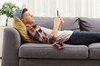 Young guy lying on a sofa and looking at a mobile phone