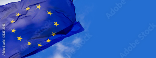 Fotografia Flag of the European Union waving in the wind on flagpole against the sky with c