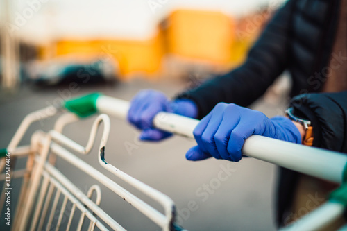 Fototapeta Close-up view of hands in rubber gloves pushing shopping carts.