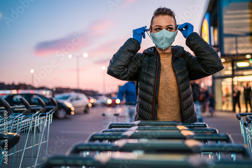 Fototapeta A woman wears medical protective gloves and a mask while shopping groceries
