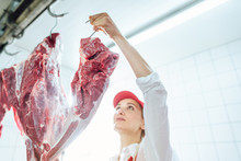 Butcher Woman Taking Meat From...